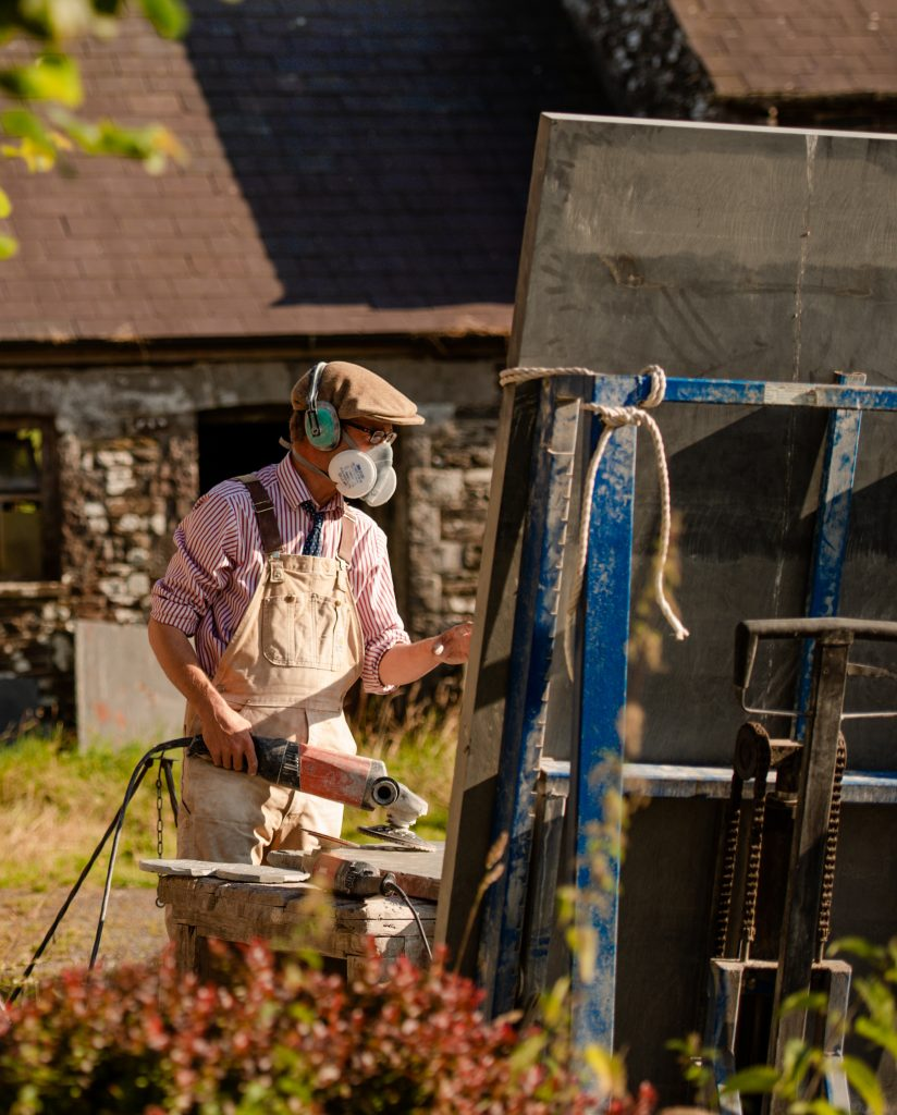 Gabriel Hummerstone carving outside his workshop on a gravestone